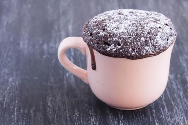 Шоколадный торт посыпанный сахарной пудрой в белой кружке