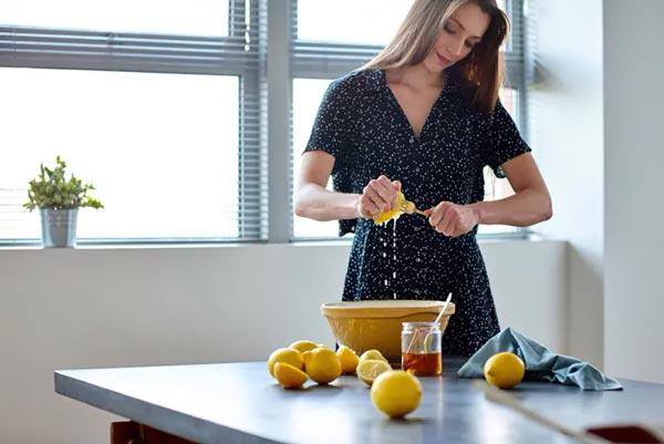 Женщина выжимает лимонный сок в миску.