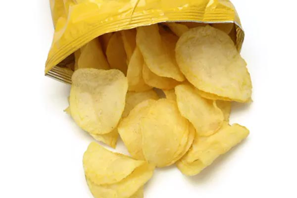Открытый пакет картофельных чипсов, из которого высыпались чипсы.