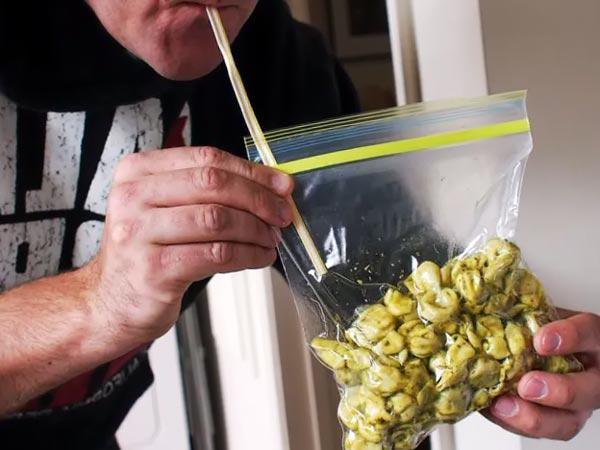 Человек, использующий соломинку, чтобы высосать воздух из мешка, полного макарон.