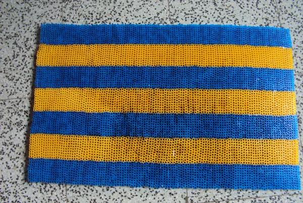Сине-желтый коврик, сделанный из соломинок.