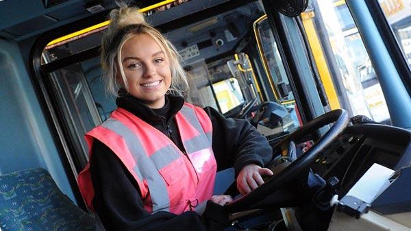 Молодая женщина за рулем автобуса общественного транспорта