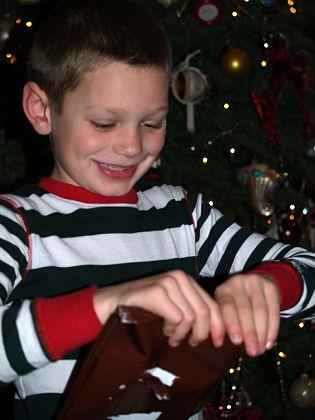 Радость на лице мальчика, открывающего подарки